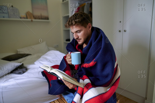 Young man wrapped in blanket reading book with coffee mug in bedroom at home