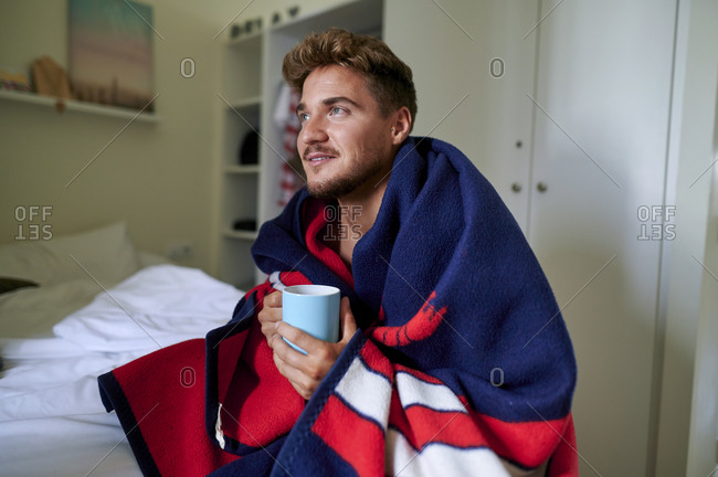 Thoughtful man wrapped in blanket holding coffee mug while sitting in bedroom at home