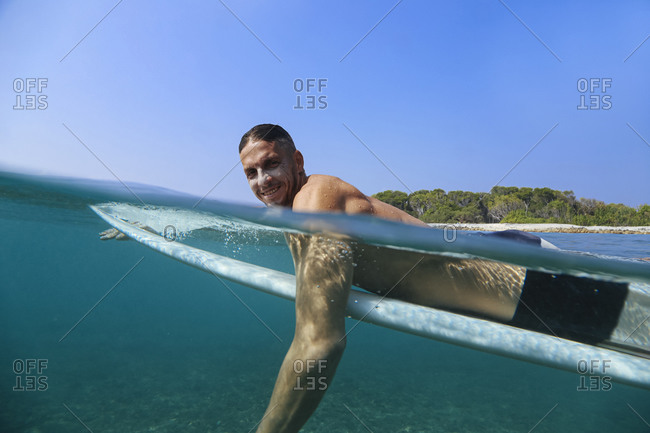 Man on surfboard swimming in sea against sky