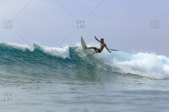 Man with surfboard surfing on wave against clear sky