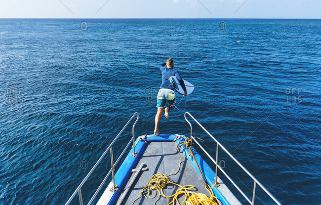 Male surfer with surfboard jumping in sea from boat deck