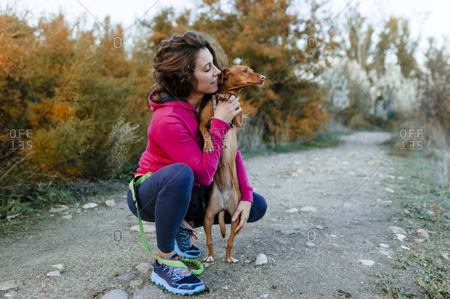 Mid adult woman looking at her dog while crouching on pathway at countryside