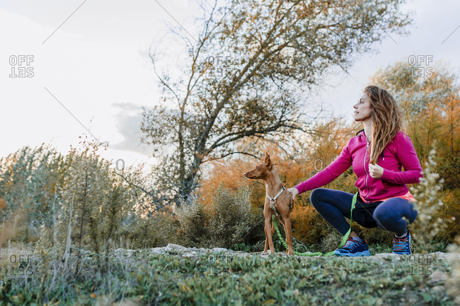Woman with brown hair with her dog looking away at countryside