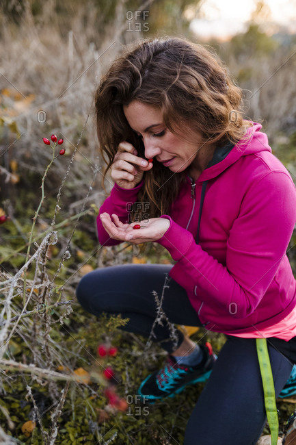Mid adult woman smelling flower bud at countryside