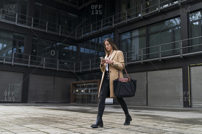 Fashionable businesswoman using mobile phone while walking on footpath against office building