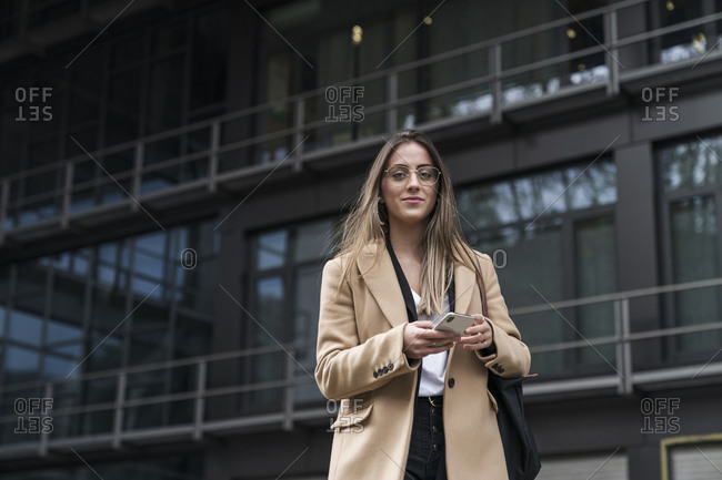 Smiling businesswoman holding mobile phone while standing against office building