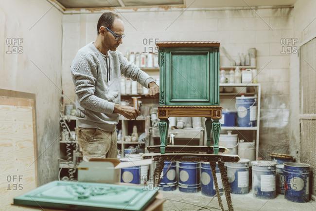 Manual worker repairing furniture while standing at workshop