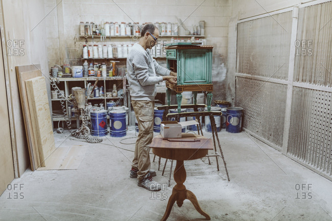Manual worker working on antique furniture while standing at workshop