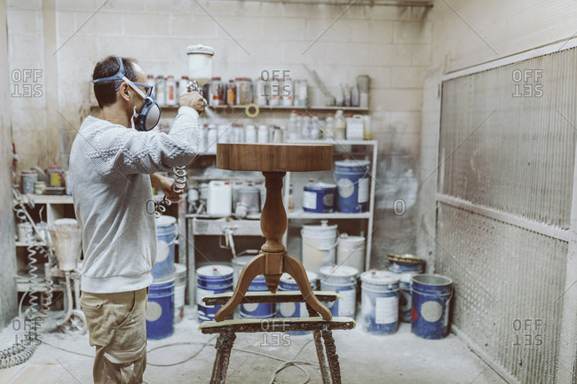 Manual worker wearing protective face mask spraying on table while standing at workshop
