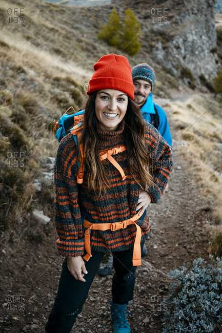 Smiling woman hiking with boyfriend on rocky mountain during vacation