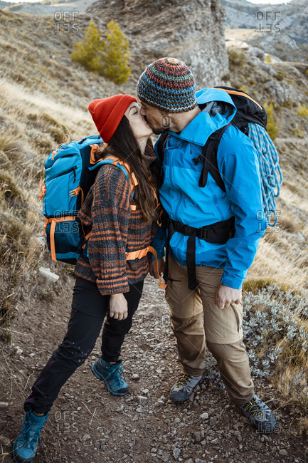 Romantic couple kissing while hiking on rock mountain during vacation