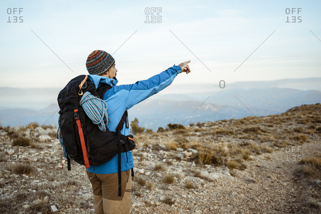 Male hiker pointing while looking at view from mountain during vacation