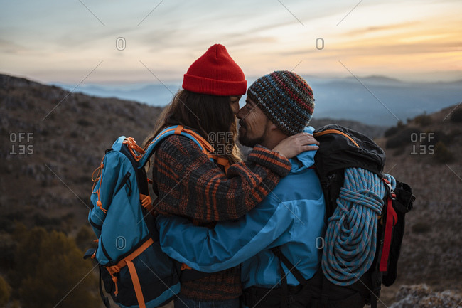 Affectionate couple standing face to face on mountain during sunset