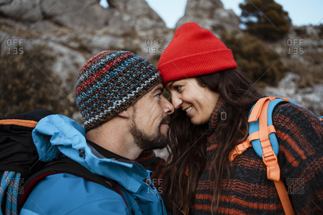 Romantic couple looking at each other while hiking on mountain