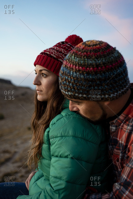 Affectionate couple on mountain during sunset