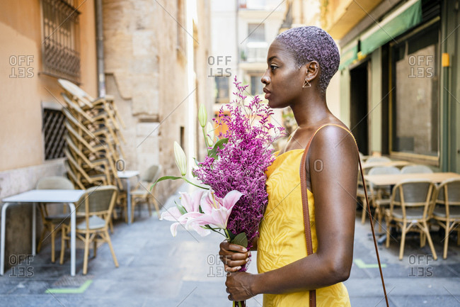 Confident female hipster holding flower bouquet in city