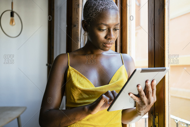 Fashionable female hipster using digital tablet while leaning on window at home
