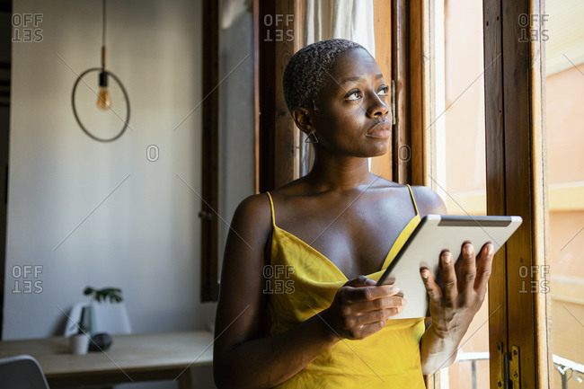 Thoughtful woman holding digital tablet while looking through window at home