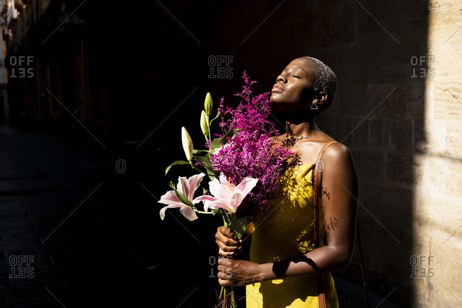 Female hipster with eyes closed holding flower bouquet on sunny day