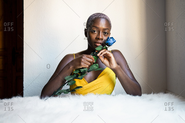 Woman with blue rose leaning on white fur against wall at home