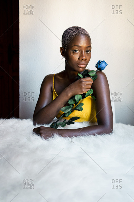 Confident woman with blue rose leaning on white fur against wall at home