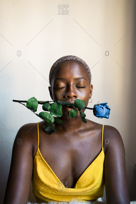 Woman closing eyes while sitting with blue rose in mouth against wall at home