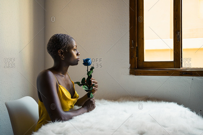 Thoughtful woman sitting with blue rose at white fur table