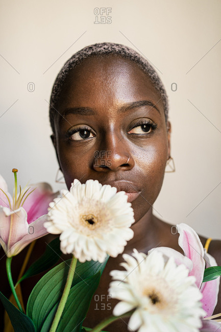 Thoughtful female hipster with flowers while looking away