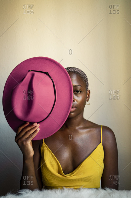 Confident woman holding pink hat in front of eye against white wall at home