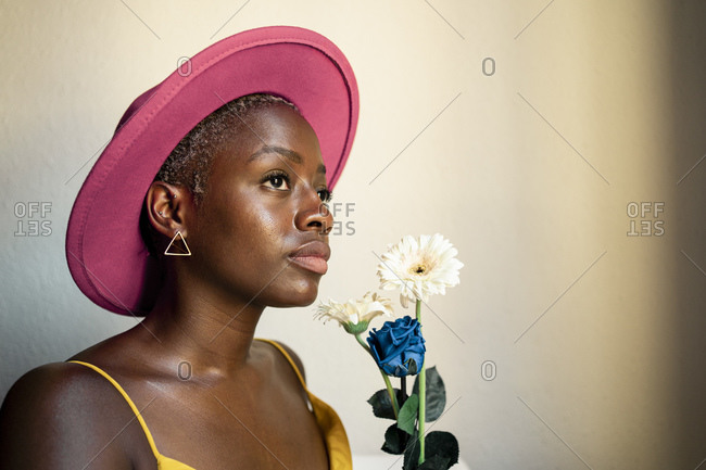 Thoughtful woman wearing pink hat holding flowers while looking away at home
