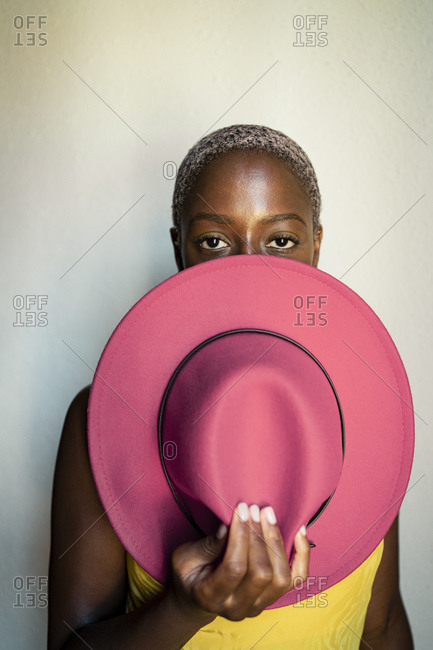 Confident woman holding pink hat in front of face against white wall at home