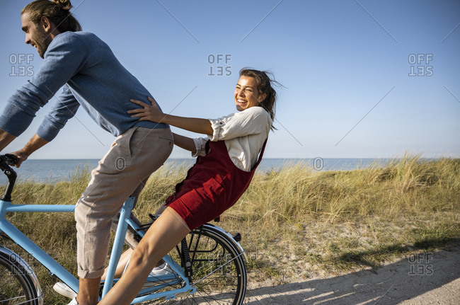 Happy woman enjoying bicycle ride with man against clear sky