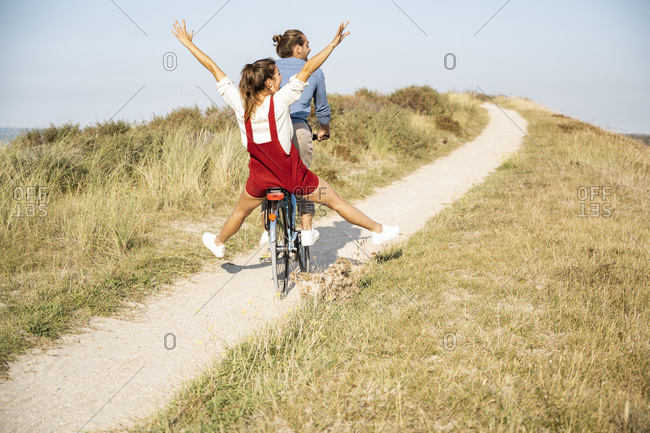 Carefree girlfriend enjoying bicycle ride with boyfriend on sunny day