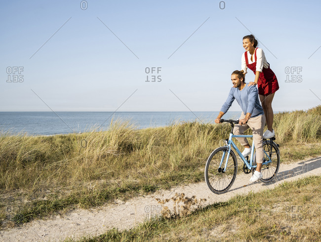 Young woman enjoying ride with man while standing on bicycle against clear sky