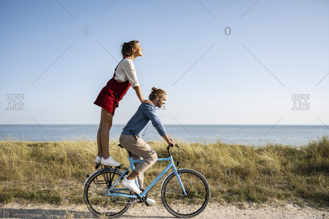 Girlfriend enjoying ride with man while standing on bicycle against clear sky