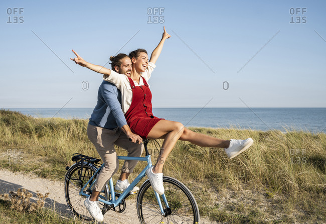Carefree couple enjoying bicycle ride against clear sky
