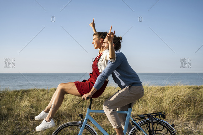 Happy couple enjoying bicycle ride together against clear sky