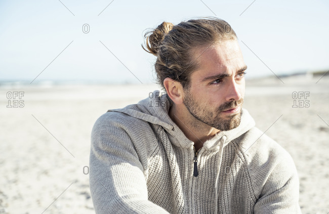 Young man wearing hooded shirt looking away while sitting on beach during sunny day