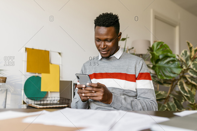 Businessman text messaging on smart phone while working from home