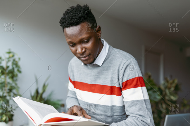 Male freelancer doing research while reading book at home
