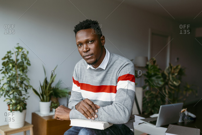 African male entrepreneur sitting with book on lap over desk while working at home