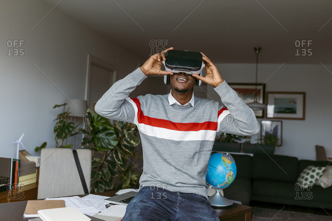 Businessman using virtual reality headset while sitting on desk at home
