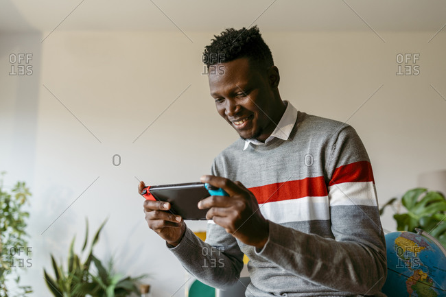 Smiling businessman playing on handheld video game at home during break from work