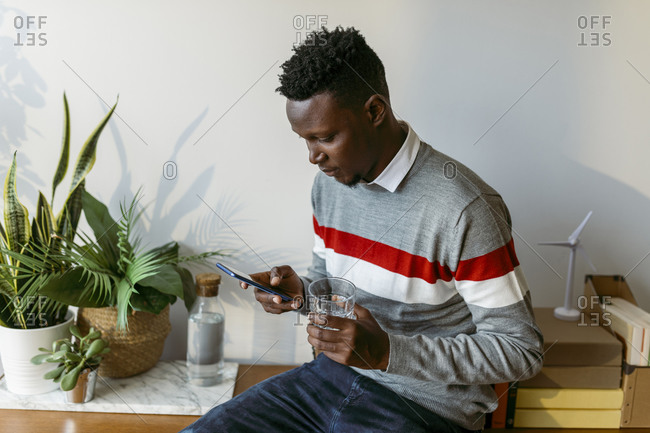 Male freelancer text messaging on smart phone while holding drinking glass at home office