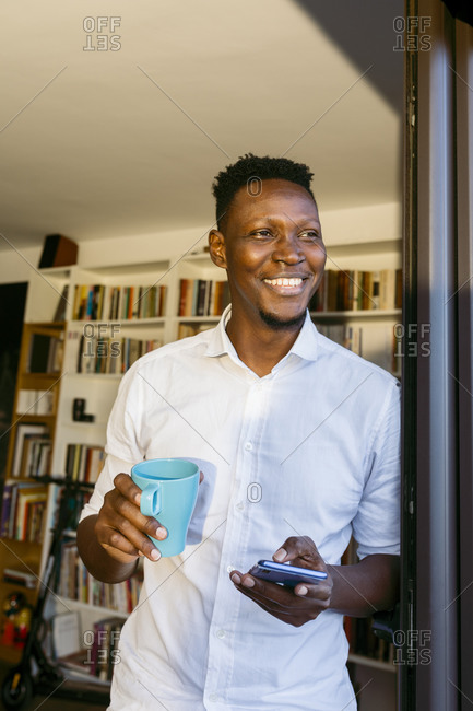 Happy businessman holding coffee cup and smart phone while leaning on doorway at home
