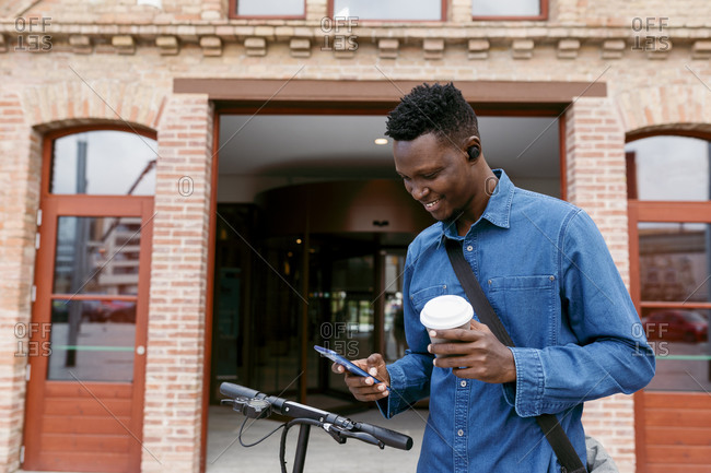 Smiling businessman using smart phone while holding reusable coffee cup against building entrance in city
