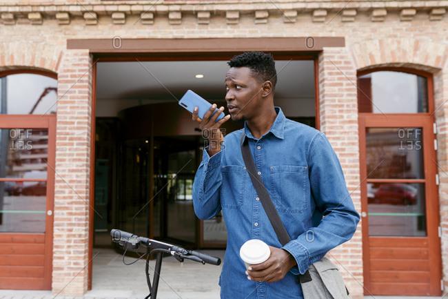 Male entrepreneur sending voicemail through smart phone while standing against building entrance