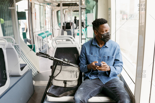 Male commuter with smart phone looking out of window while traveling through train during pandemic