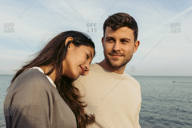 Young woman leaning on man's shoulder against sky at beach
