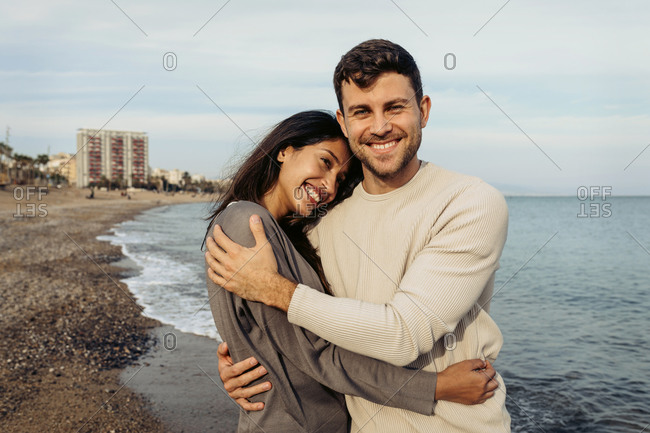 Smiling girlfriend and boyfriend embracing each other against sky at beach